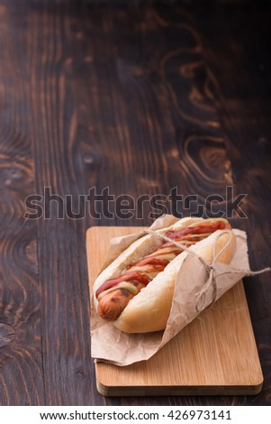 Hot dog with ketchup and mustard served on wooden board - stock photo