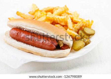 Hot dog with mustard and French fries on white background - stock photo