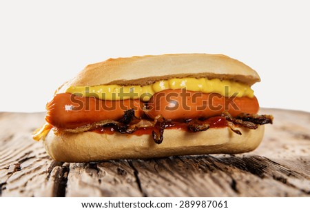 Hot dog with mustard and ketchup on wooden table and white background. - stock photo