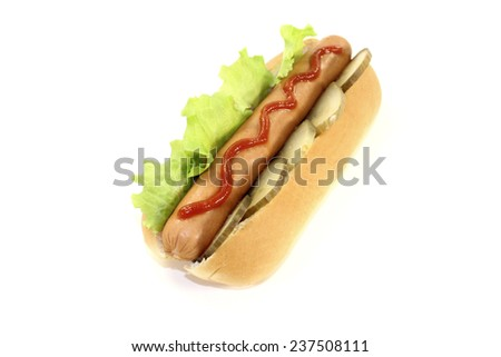 Hot dog with pickle, lettuce, sausage and ketchup - stock photo