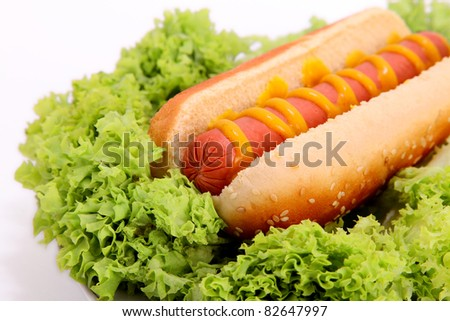 hot dog with sausage,bread and mustard over lettuce background - stock photo