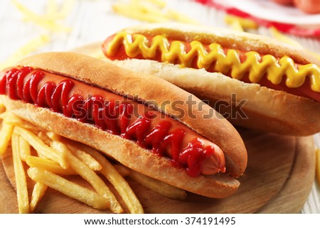 Hot dogs and fried potatoes on wooden cutting board closeup - stock photo