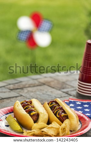 Hot dogs at a July 4th cookout are dressed with ketchup and mustard and are served with potato chips and a pickle.  Selective focus was used on this image which is one in a patriotic series. - stock photo