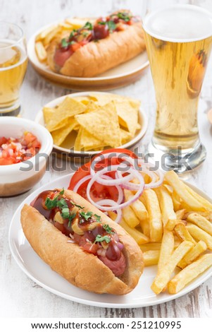 hot dogs with French fries, beer and snacks, vertical, top view - stock photo