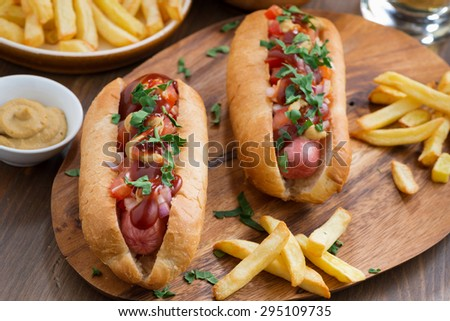 hot dogs with tomato salsa and onions on wooden board, top view, horizontal - stock photo