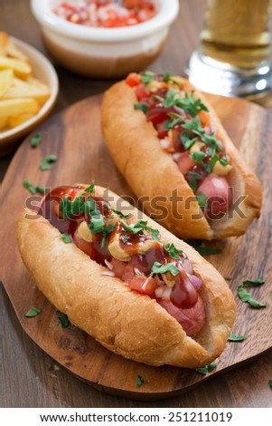 hot dogs with tomato salsa and onions, vertical, top view - stock photo
