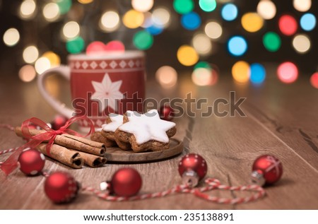 Hot drink, Christmas cookies and candy cane on decorated table  - stock photo