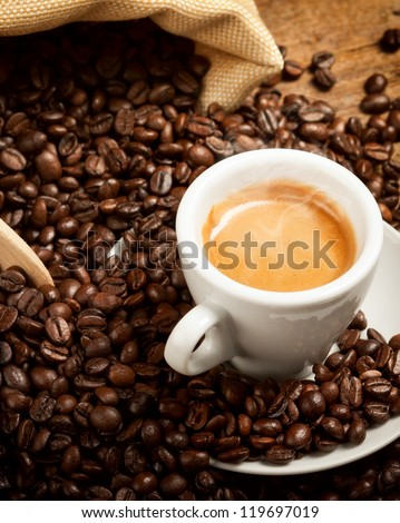 Hot espresso cup with coffee beans on wood table - stock photo