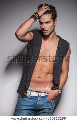 Hot fashion man fixing his hair while looking down. He is holding one hand in his pocket. - stock photo