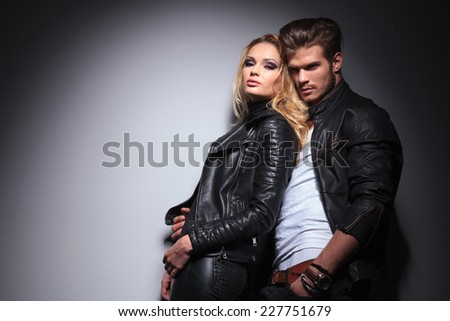 Hot fashion woman leaning on her lover while he is looking away from the camera. - stock photo