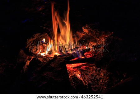Hot fire flames in the dark. majestic fire at night. a special place on the stone. concept of ecology and use of fire outdoors in travel. used as background