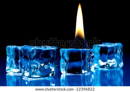 Hot flame burning on cold blue ice cubes on a reflective surface - stock photo