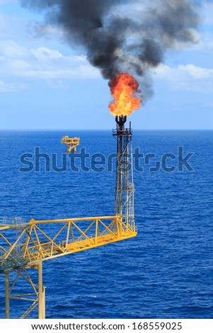 Hot flare boom and fire on offshore production platform - stock photo