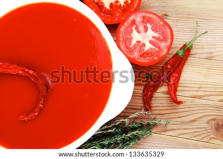 hot fresh diet tomato soup with basil thyme and raw tomatoes in white round bowl over red mat on wood table ready to eat - stock photo
