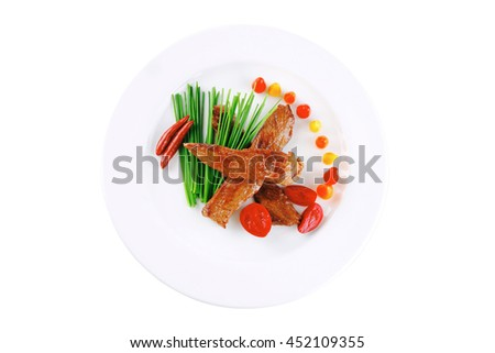 hot fresh grilled red beef meat fillet with vegetables  green chives and peppers on china plate isolated over white background - stock photo