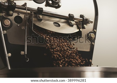 Hot freshly baked coffee beans fall from best professional large coffee roaster being poured into the cooling cylinder with motion blur on the beans Close up - stock photo