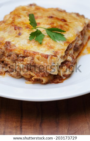 hot freshly made home lasagna, close up in plate with parsley leaf