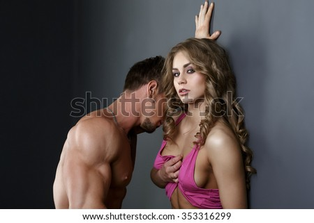 Hot girl flirting at camera, man leaned toward her - stock photo