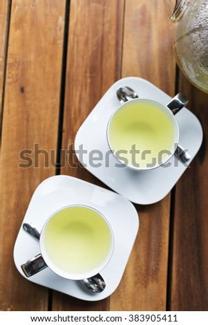 Hot green tea in cups top view - stock photo