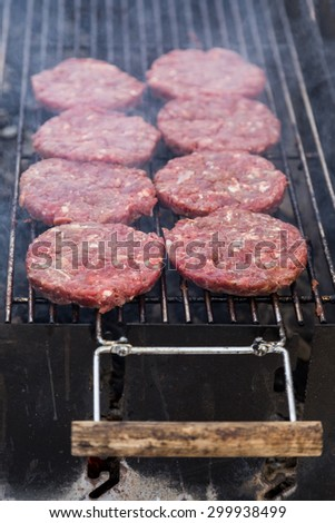 hot grill burger cutlet barbeque on grating above charcoal - stock photo