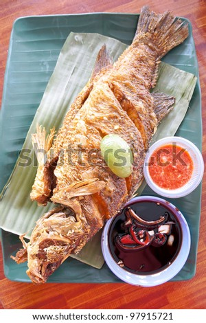 Hot grilled fish, blend in spices and layered in banana leaf - stock photo