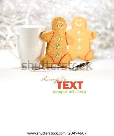 Hot holiday drink with gingerbread cookies on festive background - stock photo
