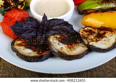Hot juicy grilled vegetables with white sauce - stock photo