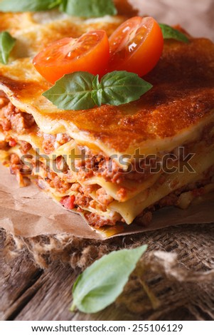 Hot lasagna with basil and tomatoes on an old table, vertical rustic style - stock photo