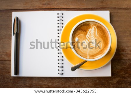 Hot latte art coffee cup on wooden table and note book. - stock photo
