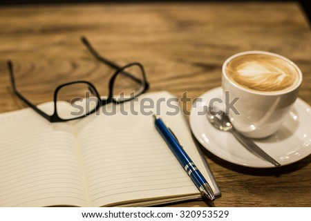 Hot latte art coffee cup on wooden table and note book, vintage and retro style. - stock photo
