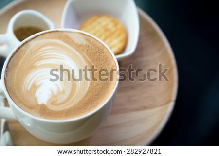 Hot latte art coffee on table - stock photo