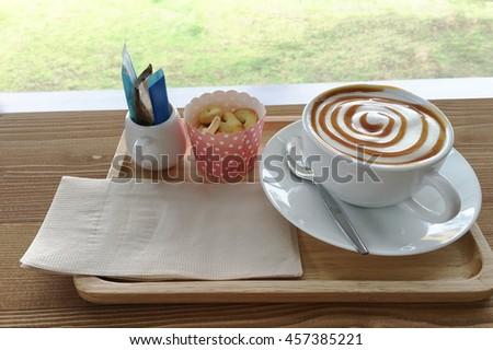 Hot Latte coffee in white dish cup,  biscuits cracker and sugar on wood table. - stock photo