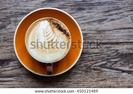 Hot latte in a orange ceramic cup  on wooden table. - stock photo