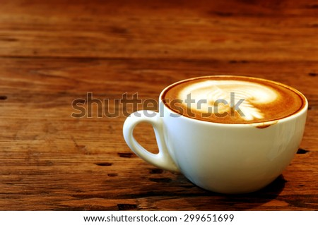 Hot latte with latte art on wooden table - stock photo