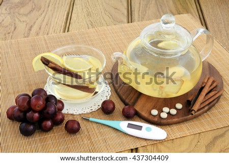 Hot lemon, honey and ginger drink for cold remedy in a glass tea cup and teapot with red grapes, cinnamon stick spice, ginseng vitamin tablets and thermometer on bamboo over oak background. - stock photo