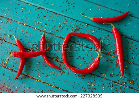 hot made with vibrant red peppers on blue wooden table background - stock photo
