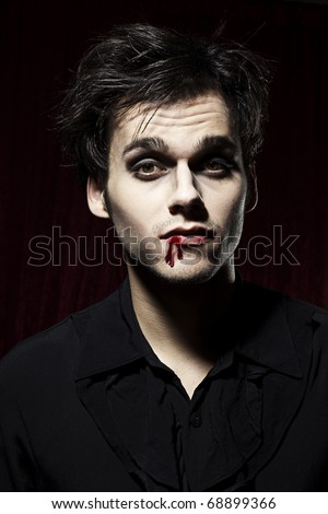 Hot male Vampire, blood on one side of his mouth. - stock photo