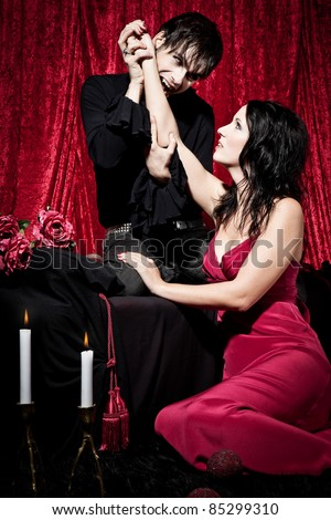 Hot male vampire is going to bite into a beautiful woman's wrist. He is kneeing on a bench, she's sitting in front of him on the floor. - stock photo