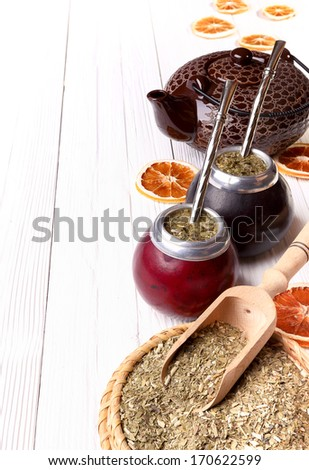 Hot mate in calabashes and set for its brewing on a light wooden background - stock photo