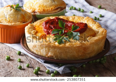 Hot meat pie on a wooden table on a plate close-up. horizontal  - stock photo