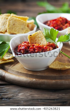 Hot mexican salsa with chili peppers and chips, selective focus