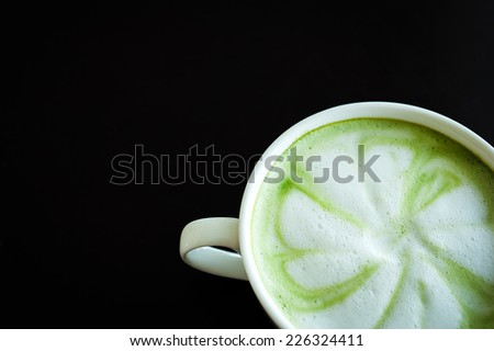 Hot milk green tea (selective focus) in the white cup on the dark wooden table. - stock photo