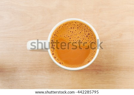 Hot milk tea in a white cup on wooden table