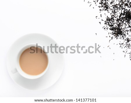 Hot milky tea with tea leaves, overhead view with plenty of copy space - stock photo