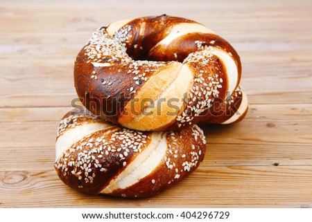 hot mixed pretzels topped by sesame seeds over wooden table - stock photo