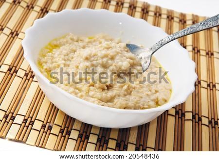 Hot morning porridge with spoon. - stock photo