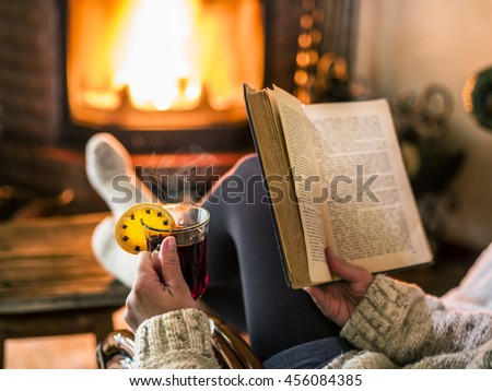 Hot mulled wine and book in woman hands. Relaxing in front of burning fire in the cold winter day. - stock photo