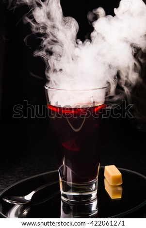 hot mulled wine with fume on a black background