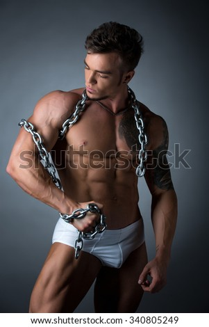 Hot muscular guy wrapped his biceps with chain - stock photo