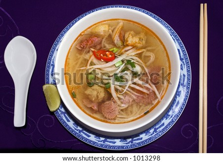 Hot noodle soup with rare beef, lemon and red hot chili. - stock photo